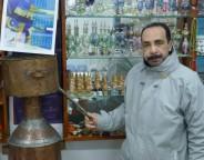Gadour, avec son distillateur, devant des flacons de parfum. (Photo CFJ / L.D-N D-M)